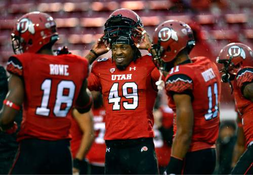 Scott Sommerdorf   |  The Salt Lake Tribune Utah WR Andre Lewis slips on his helmet after a pre game stretching as he and other Utes warm up in a steady rain prior to facing off against Washington State, Saturday, September 27, 2014.