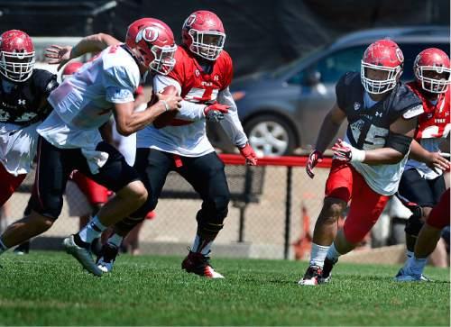 Scott Sommerdorf   |  The Salt Lake Tribune Utah DE Filipo Mokofisi, right runs to contain QB Travis Wilson who is flushed out of the pocket during Utah football practice, Saturday, August 15, 2015.