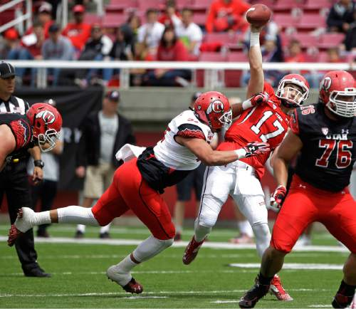 Utah's Kylie Fitts hits Utah Conner Manning (17) as he throws during the NCAA college football team's spring game Saturday, April 25, 2015, in Salt Lake City. (AP Photo/Rick Bowmer)
