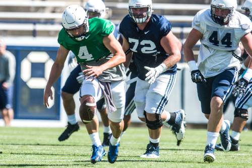 Chris Detrick  |  The Salt Lake Tribune Brigham Young Cougars quarterback Taysom Hill (4) fumbles the ball during a scrimmage at LaVell Edwards Stadium Saturday August 15, 2015.