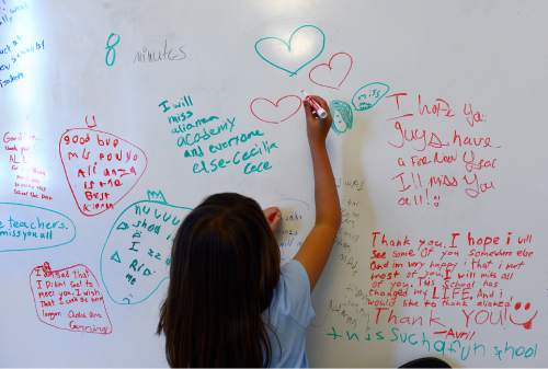 Scott Sommerdorf   |  The Salt Lake Tribune A student at Alianza Academy draws hearts on a board alongside messages other students had written written after they learned the school will permanently close its doors after Friday due to its charter being revoked by the State Charter School Board, Thursday, August 20, 2015.