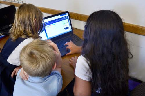 Scott Sommerdorf   |  The Salt Lake Tribune Alianza Academy 4th and 5th grade students gather around a computer during Ivana Powell's Online Class, Thursday, August 20, 2015. The school will permanently close its doors after Friday due to its charter being revoked by the State Charter School Board.