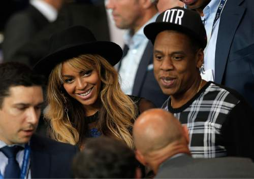 FILE - In a Tuesday, Sept. 30, 2014 file photo, Beyonce and her husband Jay Z stand up at half time in the Champions League soccer match between PSG and Barcelona, at the Parc des Princes stadium, in Paris. Beyonce announced Monday, Oct. 27, 2014 that she is merging with British retailer Topshop to launch an exercise clothing company, Parkwood TopShop Athletic Ltd. The clothing line will be available next fall. (AP Photo/Christophe Ena, File)