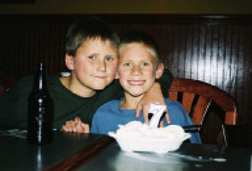 |  Courtesy Mikki Kane-Barton  Jackson Barton, left, hugs his brother during Cody's seventh birthday. The two brothers had their differences in childhood, but bonded over football and their shared heritage.