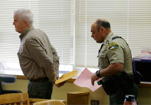 Steven Powell, left, is led away by a Pierce County Sheriff's deputy Monday, July 13, 2015, after he was found guilty in Pierce County Superior court in Tacoma, Wash., of possessing child pornography. Powell is the father of Josh Powell, who killed his two sons and himself in February 2012 while under investigation for the 2009 disappearance of his wife in Utah. (AP Photo/Ted S. Warren)