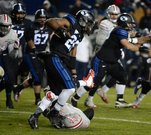 Steve Griffin  |  The Salt Lake Tribune  Brigham Young Cougars running back Adam Hine (28) gets tripped up by UNLV Rebels defensive back Mike Horsey (32) during second half action in the BYU versus UNLV football game at LaVell Edwards Stadium in Provo, Saturday, November 15, 2014.