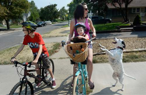 Scott Sommerdorf   |  The Salt Lake Tribune Tina Escobar-Taft and her son Tony, 12, Seth, 2, and dog Lucy are about to go on a bike ride in their Salt Lake City neighborhood, Friday, August 21, 2015.  -- Women and men who've received reproductive health care at Planned Parenthood clinics are not happy Gov. Gary Herbert is refusing to pass through federal money to the non-profit. Tina Escobar-Taft was a teenager when her mother first took her to Planned Parenthood for birth control pills, and she says the low-cost clinic helped her postpone becoming a mother until she was married and ready.