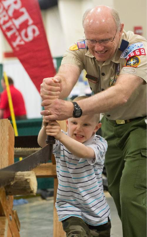 Rick Egan  |  The Salt Lake Tribune Eric Lindgren, 6, helps his grandpa, Ron Holt, saw a log with a two-man saw, at the Utah Scouting Expo at the South Towne Expo Center, Saturday, May 2, 2015.