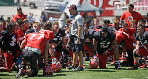 Utah coach Kyle Whittingham speaks with his team during an NCAA college football practice, Thursday, Aug. 13, 2015, in Salt Lake City. Whittingham has said the starting quarterback job is Travis Wilson's to lose. However, the competition remains open with Kendal Thompson. (AP Photo/Rick Bowmer)