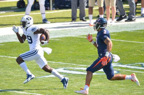 Chris Detrick  |  The Salt Lake Tribune Brigham Young Cougars wide receiver Devon Blackmon (19) runs past Virginia Cavaliers safety Quin Blanding (3) during the game at LaVell Edwards Stadium Saturday September 20, 2014.  Virginia is winning the game 16-13 at halftime.