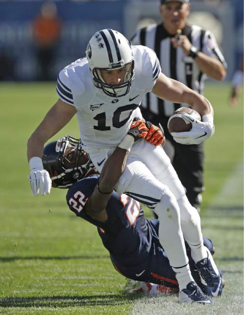 FILE - This Sept. 20, 2014, file photo, shows Virginia cornerback DreQuan Hoskey (22) tackling Brigham Young wide receiver Mitch Mathews (10) in the second half during an NCAA college football game, in Provo, Utah. BYU has visions of mismatches across the field with the 2015 passing game. That begins with a pair of 6-foot-6 receivers nicknamed the Twin Towers. With running back Jamaal Williams gone for the season, Mitch Mathews and Nick Kurtz need to live up to the hype. (AP Photo/Rick Bowmer, File)