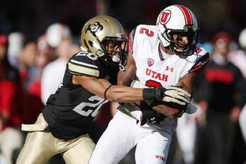 Colorado defensive back Greg Henderson, left, tackles Utah wide receiver Kenneth Scott after he pulled in a pass in the third quarter of Utah's 38-34 victory in an NCAA college football game in Boulder, Colo., on Saturday, Nov. 29, 2014. (AP Photo/David Zalubowski)
