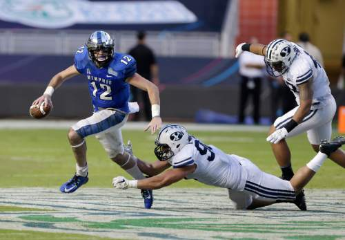 FILE -- In this Dec. 22, 2014 file photo, Memphis quarterback Paxton Lynch (12) scrambles away from Brigham Young linebacker Bronson Kaufusi, center, and defensive lineman Tomasi Laulile, right, during a 55-48 win by Memphis in the Miami Beach Bowl football game in Miami. The team matched the most wins in school history in 2014 and finishing the season on a seven-game winning streak for a 10-3 record. That gave Memphis a share of the American Athletic Conference championship and a national ranking to cap the season. (AP Photo/Wilfredo Lee, File)