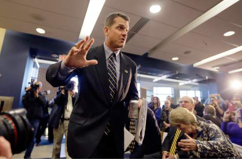 Jim Harbaugh, Michigan's new head football coach, arrives for an NCAA college football news conference where he was introduced, Tuesday, Dec. 30, 2014, in Ann Arbor, Mich. (AP Photo/Carlos Osorio)