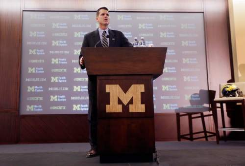Jim Harbaugh, Michigan's new head football coach, addresses the media after after he was introduced during an NCAA college football news conference Tuesday, Dec. 30, 2014, in Ann Arbor, Mich. (AP Photo/Carlos Osorio)
