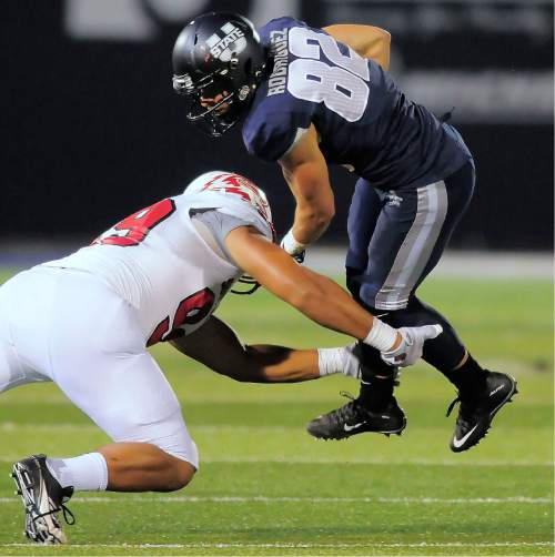 Utah State wide receiver Andrew Rodriguez (82) gets tackled by Southern Utah defensive lineman Sione Fukofuka during an NCAA college football game Thursday, Sept. 3, 2015, in Logan, Utah. (Eli Lucero/Herald Journal via AP)