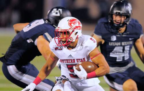 Southern Utah wide receiver Naia Ursua (5) carries the ball as Utah State linebackers Kyler Fackrell (9) and Nick Vigil (41) defend during an NCAA college football game Thursday, Sept. 3, 2015, in Logan, Utah. (Eli Lucero/The Herald Journal via AP)