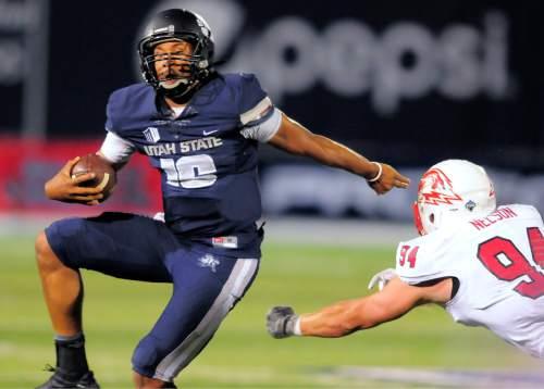 Utah State quarterback Chuckie Keeton scrambles past Southern Utah linebacker Taylor Nelson (94) during an NCAA college football game Thursday, Sept. 3, 2015, in Logan, Utah. (Eli Lucero/The Herald Journal via AP)