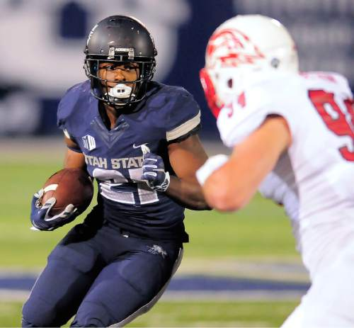 Utah State running back LaJuan Hunt (21) carries the ball as Southern Utah linebacker Taylor Nelson defends during an NCAA college football game Thursday, Sept. 3, 2015, in Logan, Utah. (Eli Lucero/The Herald Journal via AP)