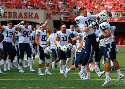 BYU Fred Warner, right, and BYU wide receiver Mitch Mathews (10) celebrate in front of other teammates after the end of the first half of an NCAA college football game against Nebraska in Lincoln, Neb., Saturday, Sept. 5, 2015. (AP Photo/Nati Harnik)