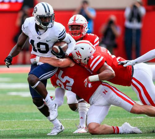 BYU wide receiver Mitch Mathews (10) is tackled by Nebraska safety Nate Gerry (25), linebacker Dedrick Young (5) and cornerback Trai Mosley (2) during the first half of an NCAA college football game in Lincoln, Neb., Saturday, Sept. 5, 2015. (AP Photo/Nati Harnik)