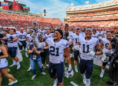 BYU players including linebacker Harvey Langi (21) and wide receiver Terenn Houk (11) celebrate their 33-28 win over Nebraska in an NCAA college football game in Lincoln, Neb., Saturday, Sept. 5, 2015. (AP Photo/Nati Harnik)
