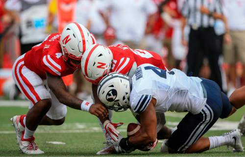 Nebraska quarterback Tommy Armstrong Jr. (4) drops the ball during a handoff to running back Mikale Wilbon (21) which is recovered by BYU linebacker Fred Warner (4) for a turnover, during the first half of an NCAA college football game in Lincoln, Neb., Saturday, Sept. 5, 2015. (AP Photo/Nati Harnik)
