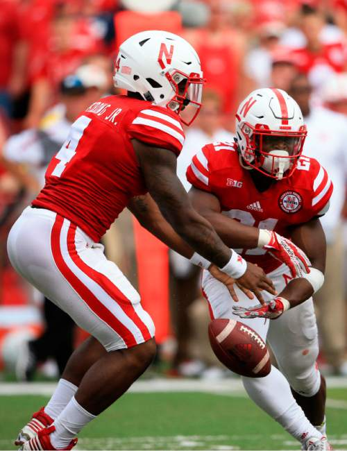Nebraska quarterback Tommy Armstrong Jr. (4) drops the ball during a handoff to running back Mikale Wilbon (21) which was recovered by BYU linebacker Fred Warner, unseen, for a turnover, during the first half of an NCAA college football game in Lincoln, Neb., Saturday, Sept. 5, 2015. (AP Photo/Nati Harnik)