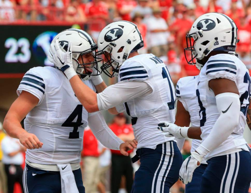 BYU quarterback Taysom Hill (4) and running back Adam Hine, right, celebrate with wide receiver Mitch Mathews (10) after Mathews scored a touchdown against Nebraska during the first half of an NCAA college football game in Lincoln, Neb., Saturday, Sept. 5, 2015. (AP Photo/Nati Harnik)