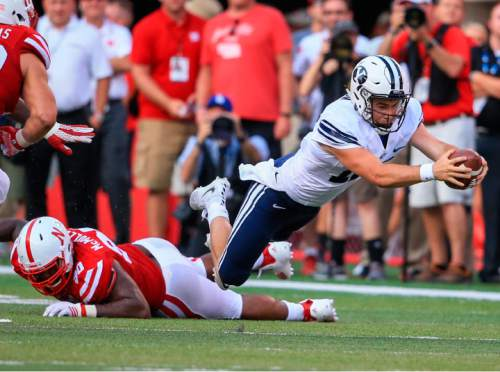 BYU quarterback Tanner Mangum (12) leaps for extra yards after being tripped by Nebraska defensive end Greg McMullen (90) during the second half of an NCAA college football game in Lincoln, Neb., Saturday, Sept. 5, 2015. BYU won 33-28. (AP Photo/Nati Harnik)