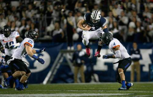 Scott Sommerdorf      The Salt Lake Tribune BYU QB Taysom Hill inexplicably jumps near the end of a scramble as he was about to be sandwiched by Boise State Broncos safety Dillon Lukehart (28)and Boise State Broncos safety Darian Thompson (4). BYU held a 24-3 lead over Boise State at the half, Friday, October 25, 2013.