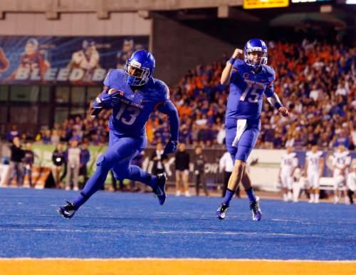 Boise State running back Jeremy McNichols (13) scores as quarterback Ryan Finley (15) celebrates, during an NCAA college football game against Washington on Friday, Sept. 4, 2015, in Boise, Idaho. (Joe Jaszewski/The Idaho Statesman via AP)