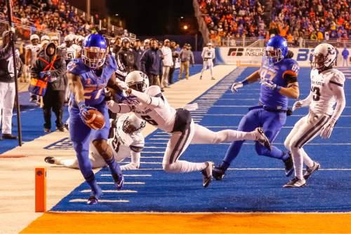Boise State running back Jay Ajayi (27) scores a touchdown past Utah State cornerback Rashard Stewart (6) during the first quarter of an NCAA college football game in Boise, Idaho, on Saturday, Nov. 29, 2014. (AP Photo/Otto Kitsinger)