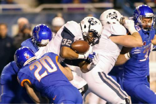 Utah State running back Joe Hill (32) is tackled by Boise State linebacker Tanner Vallejo (20) and defensive tackle Armand Nance, left rear, during the first quarter of an NCAA college football game in Boise, Idaho, Saturday, Nov. 29, 2014. Boise State won 50-19. (AP Photo/Otto Kitsinger)
