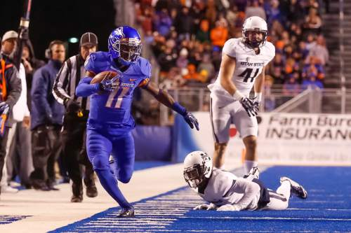 Boise State wide receiver Shane Williams-Rhodes (11) runs the ball down the sideline past Utah State cornerback Jalen Davis, bottom, and linebacker Nick Vigil (41) during the first quarter of an NCAA college football game in Boise, Idaho, on Saturday, Nov. 29, 2014. Boise State won 50-19. (AP Photo/Otto Kitsinger)