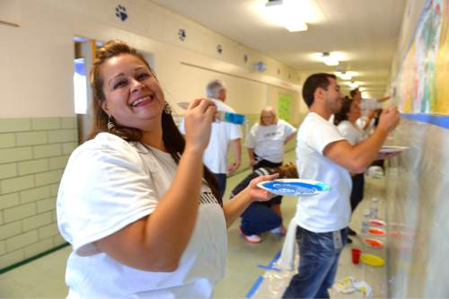 "Leah Hogsten  |  The Salt Lake Tribune ""It's a bigger brush,"" said volunteer Suzie Huerta while laughing after a co-worker praised her for her efficient and quick painting skills. Questar volunteers painted seven murals inside South Kearns Elementary School  depicting school concepts including Utah history, American history, space and the seasons during United Way of Salt Lake's Day of Caring, September 10, 2015."