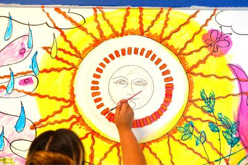 Leah Hogsten  |  The Salt Lake Tribune Maggie Barajas uses water-based polymer paint for the Wabi Sabi mixed media style mural on one wall. Questar volunteers painted seven murals inside South Kearns Elementary School  depicting school concepts including Utah history, American history, space and the seasons during United Way of Salt Lake's Day of Caring, September 10, 2015.