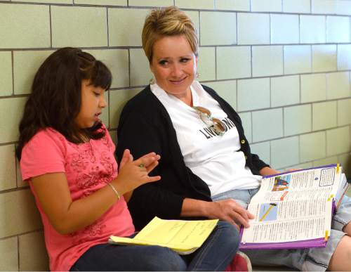 Leah Hogsten  |  The Salt Lake Tribune Volunteer Amy Allen and 4th grader Paloma Romero work on her vocabulary homework in the hall of the school. Questar volunteers painted seven murals inside South Kearns Elementary School  depicting school concepts including Utah history, American history, space and the seasons during United Way of Salt Lake's Day of Caring, September 10, 2015.