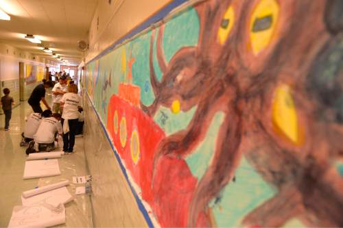 Leah Hogsten  |  The Salt Lake Tribune Questar volunteers painted seven murals inside South Kearns Elementary School  depicting school concepts including Utah history, American history, space and the seasons during United Way of Salt Lake's Day of Caring, September 10, 2015.
