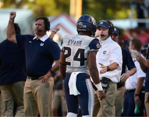 Scott Sommerdorf   |  The Salt Lake Tribune Utah State Aggies head coach Matt Wells meets Utah State Aggies safety Marwin Evans (24) on the sidelines after Evans was ejected for spearing Utah Utes wide receiver Britain Covey (18) in the end zone. Evans was ejected on the play. Utah and Utah State were tied 14-14 at the half at Rice-Eccles, Friday, September 11, 2015.