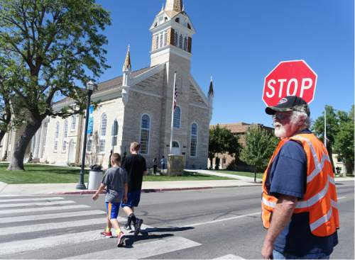 Lennie Mahler  |  The Salt Lake Tribune  A crossing guard who asked to be identified as J.R. helps children cross by the newly-restored LDS Tabernacle on Main Street in Manti, Utah, on Friday, Sept. 11, 2015. The Tabernacle will be open to the public for viewing Saturday and Sunday from 3-7 p.m.