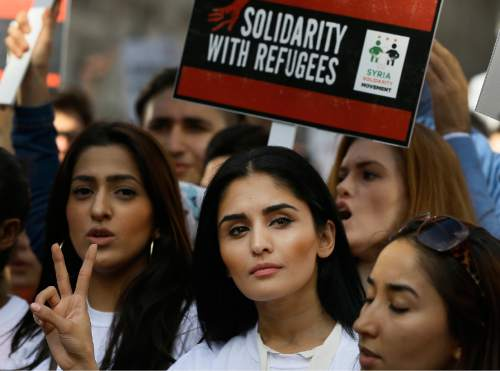 Demonstrators gesture and hold banners during a Solidarity with Refugees march from Marble Arch to Parliament in London, Saturday, Sept. 12, 2015. (AP Photo/Kirsty Wigglesworth)