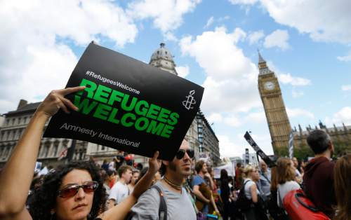 Demonstrators hold banners during a Solidarity with Refugees march from Marble Arch to Parliament in London, Saturday, Sept. 12, 2015. (AP Photo/Kirsty Wigglesworth)