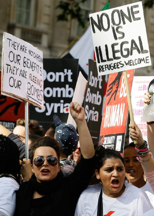 Demonstrators chant and hold banners during a Solidarity with Refugees march from Marble Arch to Parliament in London, Saturday, Sept. 12, 2015. (AP Photo/Kirsty Wigglesworth)
