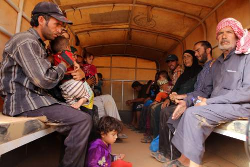 In this Thursday, Sept. 10, 2015 photo,  Syrian refugees sit in a Jordanian army vehicle after crossing into Jordanian territory with their families, in the Roqban reception area, near the northeastern Jordanian border with Syria, and Iraq, near the town of Ruwaished, 240 km (149 miles) east of Amman. The United Nations' refugee agency has urged Jordan to speed up security vetting for Syrian refugees, who must wait for weeks in a remote desert area during the process. (AP Photo/Raad Adayleh)