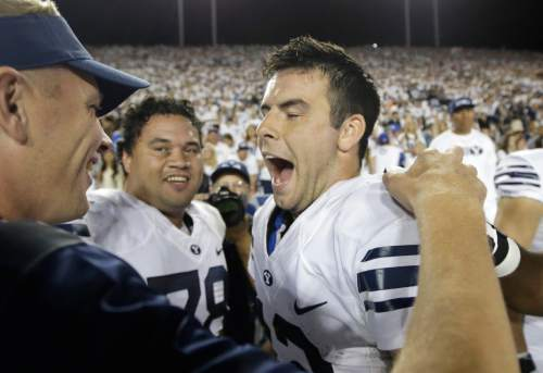 BYU quarterback Tanner Mangum, right, celebrates on the sidelines in the second half during an NCAA college football game against Boise State Saturday, Sept. 12, 2015, in Provo, Utah. BYU won 35-24.(AP Photo/Rick Bowmer)