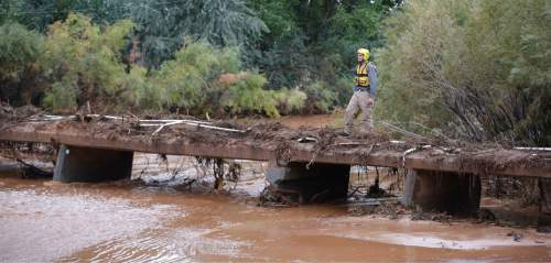A member of a search and rescue team scans a stream after a flash flood Tuesday, Sept. 15, 2015, in Colorado City, Ariz. Officials say the bodies of two people killed in flash flooding in southern Utah were recovered in Arizona about two and a half miles downstream, while the bodies of six others were recovered in Utah. Crews worked Tuesday morning to clear thousands of tons of mud and debris from the sister towns of Hildale, Utah, and Colorado City, Arizona. (AP Photo/Rick Bowmer)