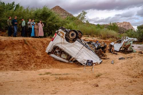 Trent Nelson  |  The Salt Lake Tribune People take in the scene in a Hildale wash where two vehicles came to rest after a flash flood that killed nine people (with four still missing) Tuesday September 15, 2015., the day after an SUV and a van were washed off a road during a flash flood in this polygamous Utah-Arizona border community.