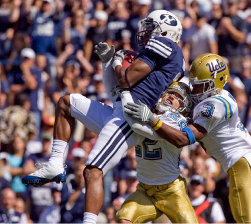 Rick Egan     The Salt Lake Tribune  UCLA CB Michael Norris (22)  and UCLA DB Rahim Moore (3) try to stop BYU wide receiver Michael Reed (3) from scoring a touchdown for the cougars, but were unsuccessful, in football action, BYU vs UCLA at Lavell Edwards Stadium in Provo.  The Cougars shut out the Bruins 59-0 Saturday, September 13, 2008.