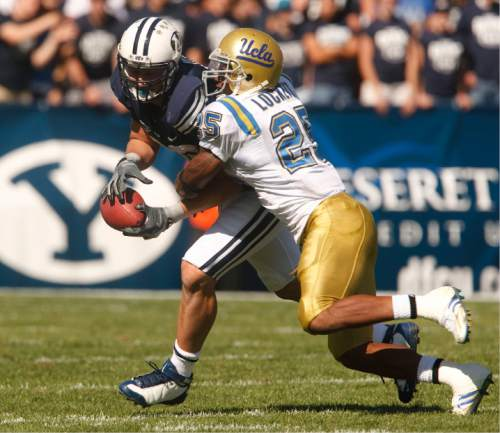 Rick Egan     The Salt Lake Tribune  BYU defensive back Andrew Rich (22) hangs on to the ball as he is hit by UCLA's Bret Locket (25)  in football action, BYU vs UCLA at Lavell Edwards Stadium in Provo.  The Cougars shut out the Bruins 59-0 Saturday, September 13, 2008.